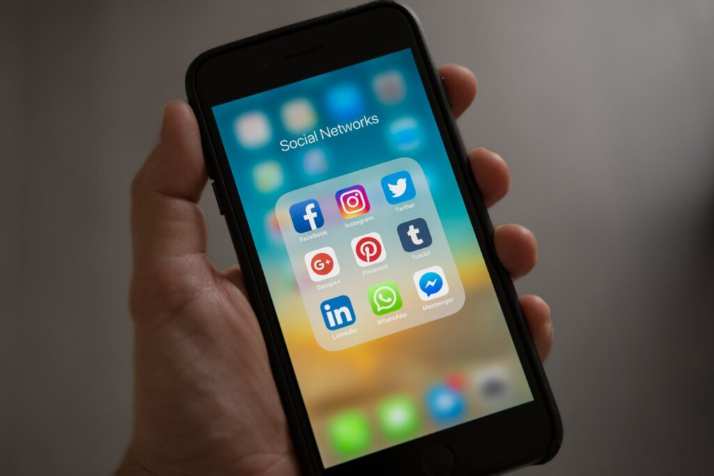 Hand holding a phone with social media icons